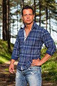 Good looking lumberjack man with blue shirt in forest. — Stock Photo