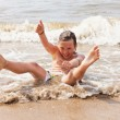 Stock Photo: Kid boy having fun at the beach in the waves of the ocean.
