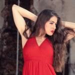 Sensual fashion woman wearing red dress posing in old urban buil — Stock Photo