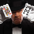 Magician with black suit and hat holding set of cards. Studio sh — Stock Photo