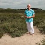 Постер, плакат: Retired senior man walking outdoors in grass dune landscape Wea