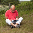 Senior retired man sitting with tablet outdoors in meadow. Scott — Stock Photo #29837875
