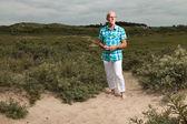 бывший старший мужчина ходьбе на открытом воздухе в траве дюна пейзаж. wea — Стоковое фото