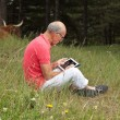 Senior retired man sitting with tablet outdoors in meadow. Scott — Stock Photo #29843535