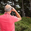 Senior man using binoculars outdoors. Watching scottish highland — Stock Photo