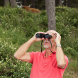Senior retired man with beard using binoculars outdoors. Wearing — Stock Photo