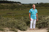Retired senior man with beard and glasses outdoors in grass dune — Stock Photo