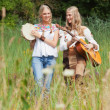Two retro blonde 70s hippie girls making music with acoustic gui — Stock Photo #30258417