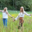 Two retro blonde 1970s hippie girls with sunglasses dancing in f — Stock Photo