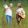 Two retro blonde 70s hippie girls making music with acoustic gui — Stock Photo
