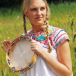 Retro blonde 70s hippie girl with tambourine outdoor in nature.  — Stock Photo