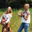 Two retro blonde 70s hippie girls making music with acoustic guitar and tambourine outdoor in nature. — Stock Photo
