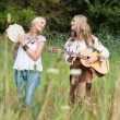 Two retro blonde 70s hippie girls making music with acoustic gui — Stock Photo #30258701