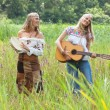 Two retro blonde 70s hippie girls making music with acoustic gui — Stock Photo #30258723