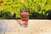 Glas färsk rosa soda på balkongen med suddiga grön trädgård ba — Stockfoto