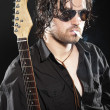 Rock guitarist with long brown hair and beard and sunglasses dre — Stock Photo