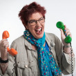 Stressed middle aged woman screaming and holding two vintage tel — Stock Photo #31610373