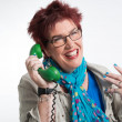 Middle aged woman calling with vintage green telephone. Red shor — Stock Photo