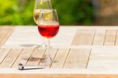 Glass of rose wine on wooden garden table with hotel key. Blurre — Stock Photo