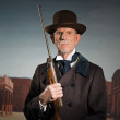Senior western man wearing a brown hat and coat holding rifle. S — Stock Photo #33511807