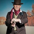 Senior western man wearing a brown hat and coat holding a revolv — Stock Photo #33512095