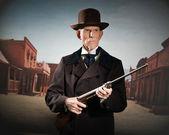 Homem ocidental sênior usando um chapéu marrom e o casaco, segurando o rifle. s — Fotografia Stock