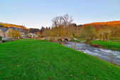 Rural landscape with old bridge over streaming river in autumn. — Stock Photo