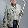 Smiling senior gardener mwith hat holding hoe. Studio shot ag — Stock Photo #36636457
