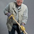 Smiling senior gardener mwith hat holding hoe. Studio shot ag — Stock Photo #36636479