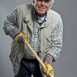Stock Photo: Smiling senior gardener mwith hat holding hoe. Studio shot ag