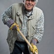 Smiling senior gardener mwith hat holding hoe. Studio shot ag — Stock Photo #36636529