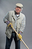 Gardener senior man with hat holding hoe. Studio shot against gr — Stock Photo