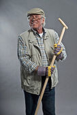 Smiling senior gardener man with hat holding hoe. Wearing glasse — ストック写真