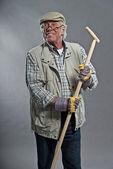 Smiling senior gardener man with hat holding hoe. Wearing glasse — Photo