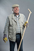 Smiling senior gardener man with hat holding hoe. Studio shot ag — Stok fotoğraf
