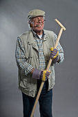 Gardener senior man with hat holding hoe. Wearing glasses and sm — Stock fotografie