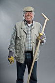 Smiling senior gardener man with hat holding hoe. Studio shot ag — ストック写真