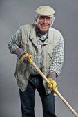 Smiling senior gardener man with hat holding hoe. Studio shot ag — Zdjęcie stockowe