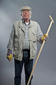Smiling senior gardener man with hat holding hoe. Studio shot ag — Стоковое фото