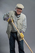 Smiling senior gardener man with hat holding hoe. Wearing glasse — Stok fotoğraf