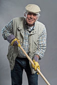 Smiling senior gardener man with hat holding hoe. Studio shot ag — Foto de Stock