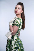 Retro fifties fashion brunette girl wearing green dress. Holding — Foto de Stock
