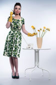 Retro 50s fashion housewife on the phone wearing yellow rubber g — Stock Photo