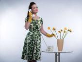 Retro anos 50 moda dona de casa no telefone usando borracha amarela g — Fotografia Stock