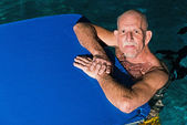 Healthy active senior man with beard in indoor swimming pool pla — Stock Photo