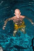 Healthy senior man with beard in indoor swimming pool. — Стоковое фото