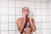 Senior man taking a shower in bathroom. — Stock Photo