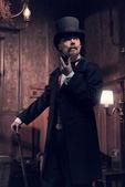 Vintage 1900 fashion man with beard. Smoking tobacco pipe. Stand — Stock Photo
