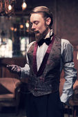 Vintage 1900 fashion man with beard. Standing in old wooden room — Stock Photo
