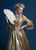 Retro baroque fashion woman wearing gold dress. Holding a fan. S — Stock Photo